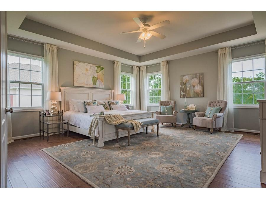 The Owner's Bedroom features a Tray Ceiling, Two Additional Windows on the Side of the Home and Hardwood Flooring.